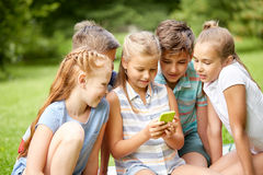 Kids or friends with smartphone in summer park. Friendship, childhood, technology and people concept - group of happy kids or friends with smartphone in summer Royalty Free Stock Photography