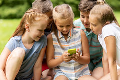Kids or friends with smartphone in summer park. Friendship, childhood, technology and people concept - group of happy kids or friends with smartphone in summer Royalty Free Stock Images