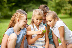 Kids or friends with smartphone in summer park. Friendship, childhood, technology and people concept - group of happy kids or friends with smartphone in summer Stock Photography