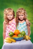 Kids and fruit. Two little girls standing at the table with fruits on the green background Stock Photography