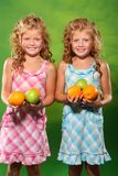 Kids and fruit. Little girls with fruit on the green background Stock Image