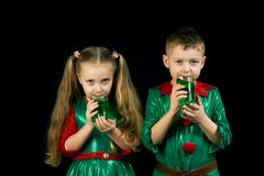Kids fun in green costumes on St. Patrick`s day. Cheerful children in green suits with a glass of green drink on St. Patrick`s day Stock Photo