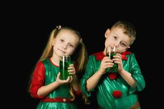 Kids fun in green costumes on St. Patrick`s day. Cheerful children in green suits with a glass of green drink on St. Patrick`s day Royalty Free Stock Photography