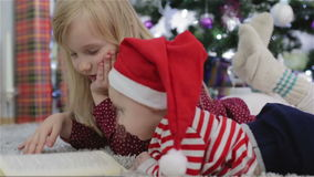 Kids fun reading a book near a Christmas tree. Girl blonde and boy in Santa hat reading a book on the floor near the Christmas decorations stock footage