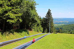 Kids fun on summer toboggan run. Summer holidays with kids having fun on a toboggan run in the countryside - at the Wasserkuppe, Germany Stock Image