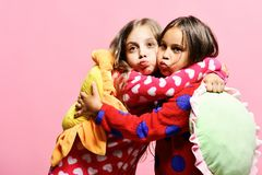 Kids with funny faces make air kisses and hold pillows. Kids with funny faces make air kisses and hold green and yellow sun pillows. Friends in pink pajamas stock image