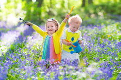 Kids in a garden with bluebell flowers Royalty Free Stock Images