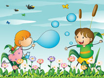 Kids at the garden playing with the blowing bubbles Stock Photo