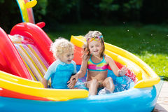 Kids in garden swimming pool with slide Royalty Free Stock Photography
