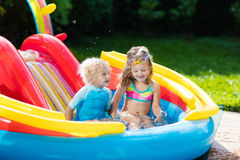 Kids in garden swimming pool with slide Royalty Free Stock Photos