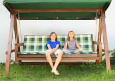 Kids on a garden swing. Barefoot boy and girl - kids sitting on a wooden garden swing Royalty Free Stock Photo