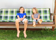 Kids on a garden swing. Barefoot kids - boy and girl sitting on a wooden garden swing Royalty Free Stock Images