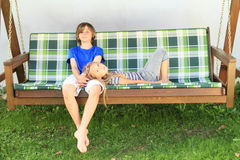 Kids on a garden swing. Kids - little girl lying on lap of her brother on a wooden garden swing Royalty Free Stock Image