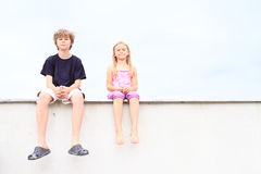 Kids - girl and boy sitting on roof Royalty Free Stock Image