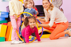 Kids with girl and teacher play active game Royalty Free Stock Photos