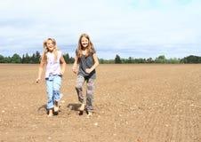 Kids - girls dancing on field. Little kids - barefoot girls dancing on ground of muddy field Royalty Free Stock Image