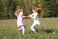 Kids - girls dancing on meadow. Little kids - girls dancing on grass of meadow with forest behind Stock Photography