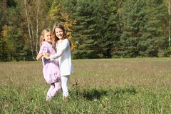 Kids - girls dancing on meadow. Little kids - girls dancing on grass of meadow with forest behind Royalty Free Stock Image