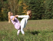 Kids - girls dancing on meadow. Little kids - girls dancing on grass of meadow with forest behind Royalty Free Stock Photo