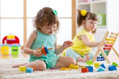 Kids are engaging in daycare. Two toddler children playing with educational toys in kindergarten. Kids girls are engaging in daycare. Two toddler children stock photos