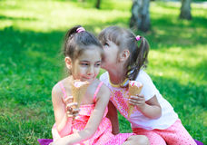 Kids girls friends children with ice cream. Two kids girls sisters whispering eating ice cream on background of grass Royalty Free Stock Images