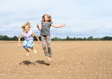 Kids - girls jumping on field Stock Image