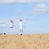 Kids - girls jumping on field. Little kids - girls jumping on ground of plowed field Stock Image