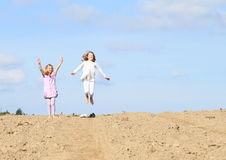 Kids - girls jumping on field. Little kids - girls jumping on ground of plowed field Royalty Free Stock Photos