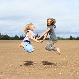Kids - girls jumping on field Stock Photos