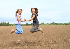 Kids - girls jumping on field Royalty Free Stock Photography