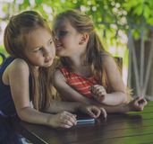 Kids girls ladies in a cafe with a tablet Royalty Free Stock Photos
