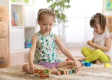 Kids girls are playing with cubes Royalty Free Stock Image