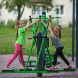 Kids girls practice gymnastics on the public sport equipment Royalty Free Stock Photos