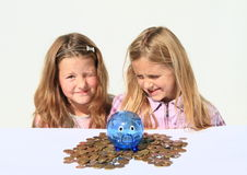 Kids - girls with saving pig full of money Stock Images