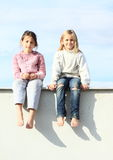 Kids - girls sitting on roof. Smiling kids - barefoot girls sitting on grey roof under the blue sky Stock Images