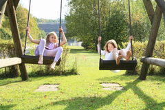 Kids - girls on swing. Barefoot kids - smiling girls in lila and white clothes sitting and swinging on swings Stock Images