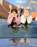 Kids - girls on windscreen of a car. Little barefoot kids - girls lying on windscreen of a silver car with reflex on hood Stock Image