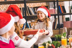 Kids giving christmas present to mother. Little kids giving christmas present to beautiful young mother Royalty Free Stock Photos