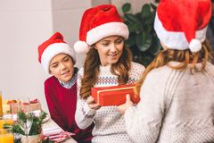 Kids giving christmas present to mother. Little kids giving christmas present to beautiful young mother Royalty Free Stock Image
