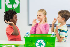 Kids giving high five to each other in classroom. At school Stock Images