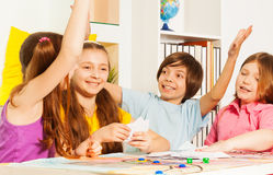 Kids giving hive five sitting at the gaming table. Happy kids giving hive five, sitting at the gaming table and playing cards at the room stock image
