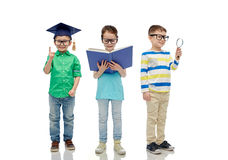 Kids in glasses with book, lens and bachelor hat Royalty Free Stock Images