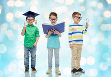 Kids in glasses with book, lense and bachelor hat Stock Photography