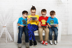 Kids in glasses with gadgets, computer addiction. Group of kids in eye glasses look into their phones and tablets. Children computer games, social networks and Royalty Free Stock Images