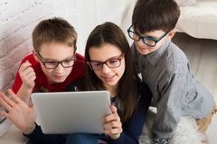 Kids in glasses with tablet, computer addiction. Group of kids in eye glasses look into tablet. Children computer games, social networks and media addiction Stock Photos