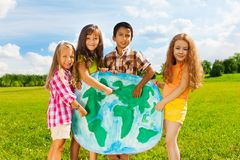 Kids with globe map. Group of happy kids boys and girls standing and pointing to the globe map depicting diversity concept standing outside Stock Photos