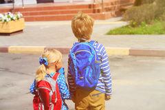 Kids go to school- little boy and girl with backpacks on the street. Kids go to school- little boy and girl with backpacks near school or daycare building royalty free stock photography