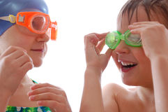Kids with goggles. Smiling elementary age boy and girl with wet hair and goggles talking royalty free stock photography