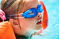 Kids with goggles in swimming pool. Stock Photo