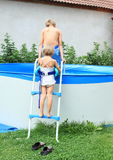 Kids going into pool Stock Photo